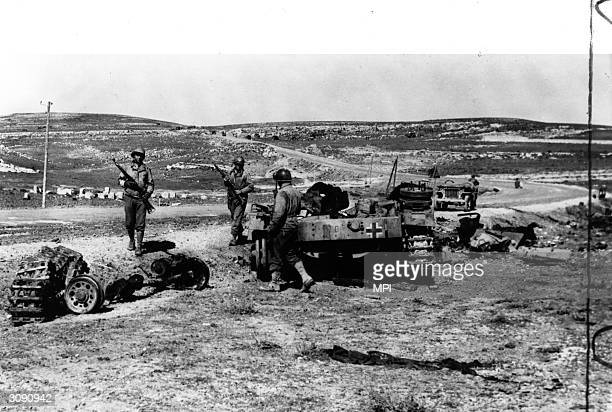 A patrol from the US army's Second Corps looking over a burnt out tank belonging to Rommel's Afrika Korps following the Battle of Kasserine Pass...