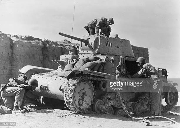 American soldiers examine an Italian tank captured during a successful counterattack at the Kasserine Pass southeastern Tunisia scouring it for booby...