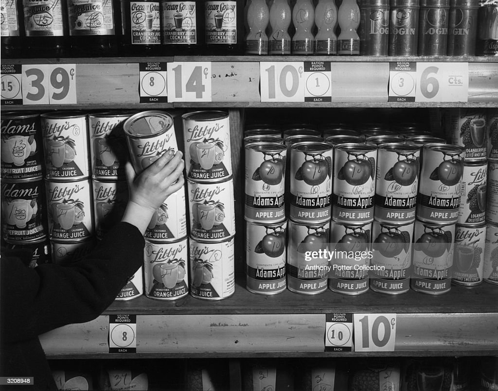 Someone reaches for a can of orange juice from a grocery shelf during World War II. Cards indicating 'Ration Points Required' for various canned foods helped America's wartime marketers in using War Ration Book Two.