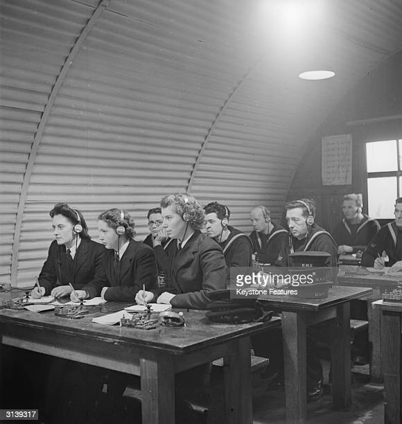 Wrens and Bluejackets taking down messages in Morse code in the Morse Instructional Room on board HMS Mercury, the Royal Navy's Signal Training...