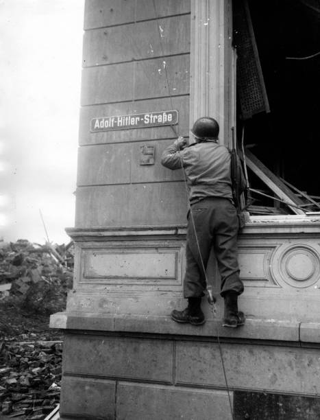 An American GI removing a sign which reads 'Adolf Hitler...