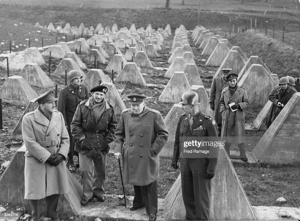 British Prime Minister Winston Churchill visits the US 9th Army as they cross the concrete barrier of the Siegfried Line or West Wall into Germany, during World War II. With him are (left to right) General Simpson, Commander-in-Chief of the 9th Army, Field-Marshal Montgomery and Field-Marshal Sir Alan Brooke.