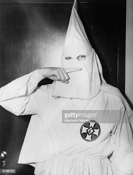 Stetson Kennedy author of the Ku Klux Klan study 'Southern Exposure' posing in the Klan's uniform to illustrate the sign indicating the Oath Of...