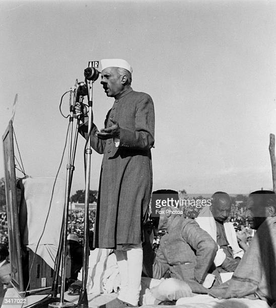 Indian politician and Prime Minister Pandit Jawaharlal Nehru paying tribute to the Indian statesman and advocate of nonviolence Mahatma Gandhi at a...