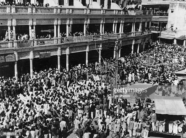 Vast crowds follow the body of assassinated Indian nationalist leader Mahatma Gandhi as it passes slowly along the funeral route to the immersion...
