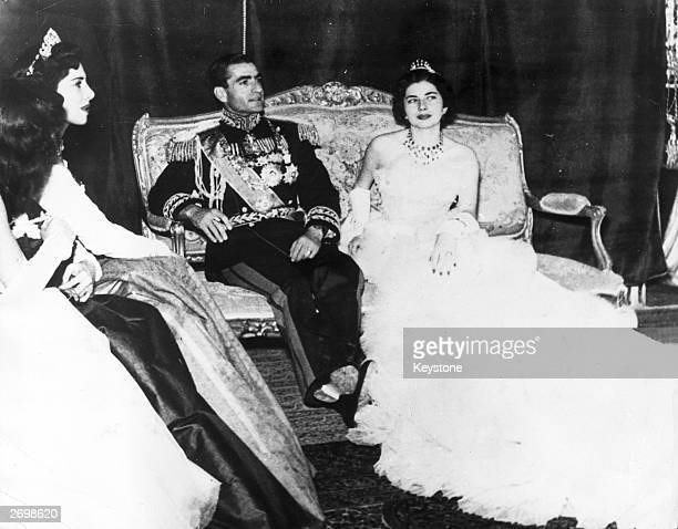 Muhammad Reza Pahlavi the Shah of Iran with his second wife Princess Soraya Esfandiary Bakhtiari after their wedding ceremony His sisters who acted...