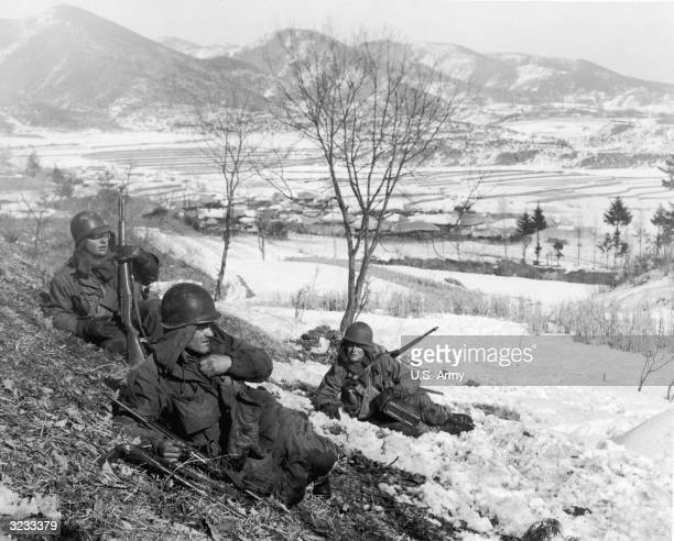 Three US soldiers rest on a snowy hillside after successfully assaulting enemy positions in the vicinity Korea Korean War