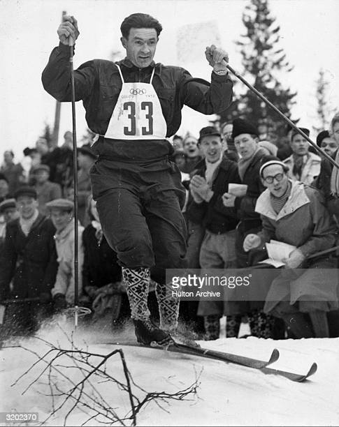 Full-length image of Norwegian skier Simon Slattvik crossing the finish line to take the gold medal in the 18 km Long Distance Run, Combined Class,...