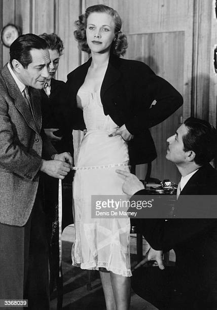 English actress Honor Blackman stripped down to her corset as Joseph Buloff and Guido Lorraine take her measurements in the play 'Fifth Season' at...