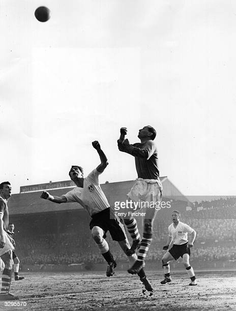 Birmingham City's goalkeeper Gil Merrick and Millwall's inside left Pacey jump for the ball during a 5th round FA Cup tie at 'The Den'