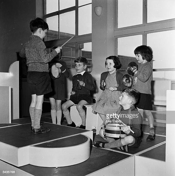 Fiveyearold Michael Gale conducts cymbalist Beverley Maynard and drummer Terence Wood as well as the other orchestra members of the Thames View...
