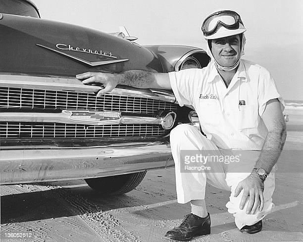 NASCAR driver Buck Baker kneels next to a brand new 1957 Chevrolet on the Daytona Beach and Road Course Baker would drive the new Chevrolet body...