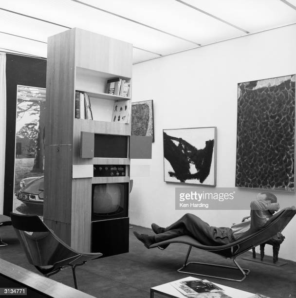 35 year old London designer Richard Hamilton relaxing with a friend in his flat equipped with a cocktail cabinet control panel for lighting...