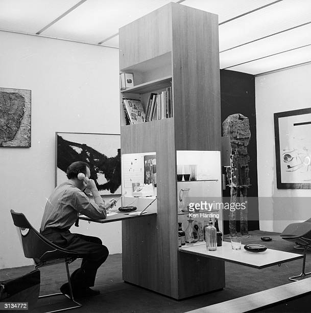 35 year old London designer Richard Hamilton relaxing in his flat equipped with a cocktail cabinet control panel for lighting bookshelves radio...