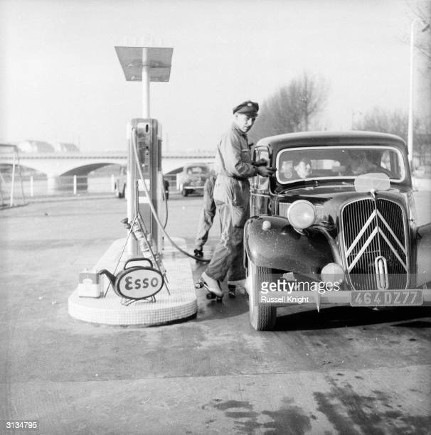 A Parisian petrol pump attendant on roller skates pours oil into a motorist's car