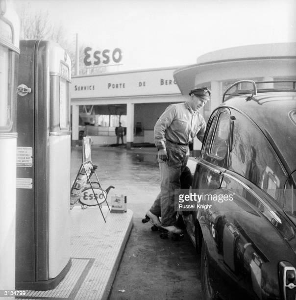 A Parisian petrol pump attendant on roller skates pours oil into a motorist's car