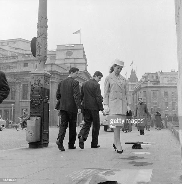 British starlet Gale Sheridan admires the work of a pavement artist outside the National Gallery in London. She is wearing a three-quarter length...