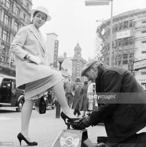 British starlet Gale Sheridan has her shoes polished by a shoeshine in Leicester Square London She is wearing a threequarter length jacket and a...