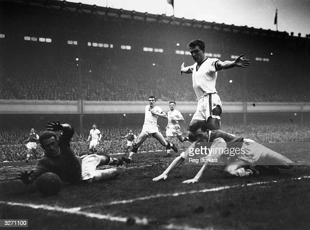 Manchester United goalkeeper Gregg makes a save He is watched by United rightback Foulkes and Duncan Edwards as Manchester United play Arsenal at...