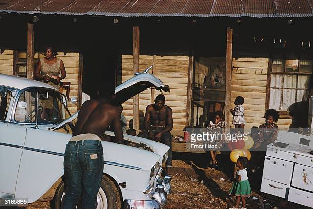 A man checks his car engine in front of a row of slum housesand their inhabitants in a shanty town in New Orleans Louisiana