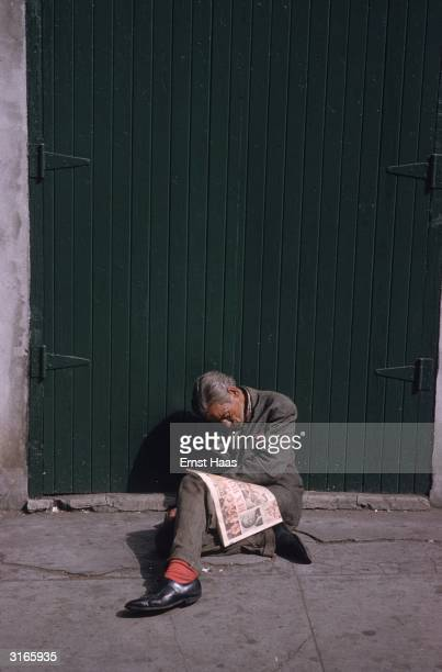 A man has fallen asleep over his newspaper leaning against a doorway in a New Orleans street