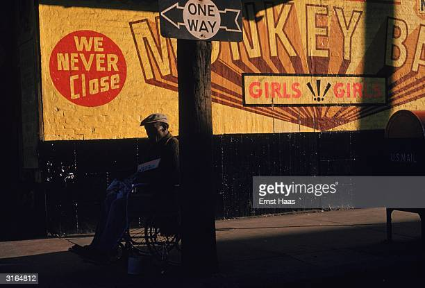 A man in a wheelchair sits out side a sign painted on a wall saying 'Monkey Bar Girls Girls We Never Close'