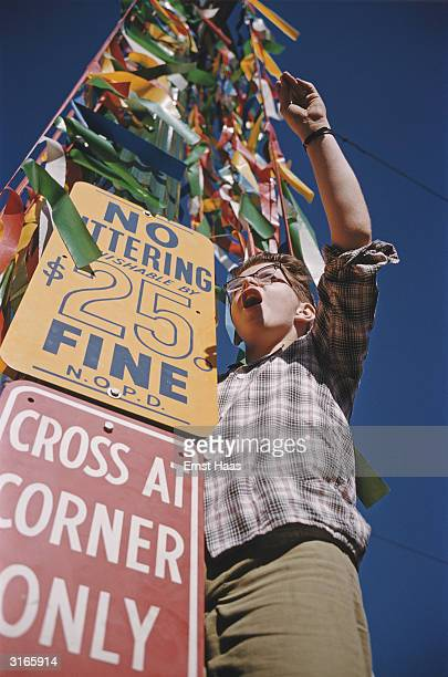A Mardi Gras reveller in New Orleans Louisiana stands by a decorated street sign which forbids littering on pain of a $25 fine