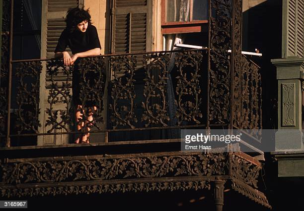 A woman on a fancy ironwork balcony watches a Mardi Gras procession in the street below