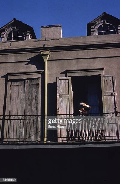 An old woman sitting on a balcony shades her eyes against the sun as she watches a Mardi Gras procession