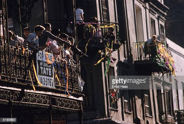 Iron work balconies in New Orleans filled with onlookers watching the Mardi Gras parade in New Orleans