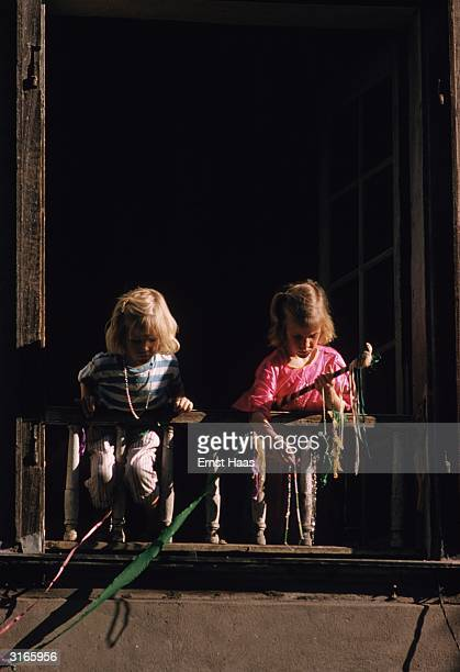 Two little girls lean over a balcony to drop streamers on a Mardi Gras procession in the street below