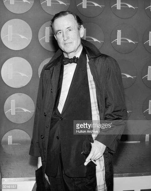 British author Ian Fleming poses in an airport holding a cigarette in a holder New York City