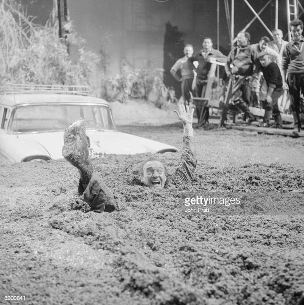 Scottish actor David Niven buried up to his neck in quicksand on the set of 'Act of Mercy' at Elstree Studios
