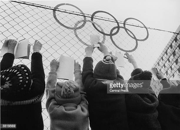 Group of children outside the fence surrounding the Olympic Village waiting for athletes or officials to sign autographs at the 1964 Winter Olympics...