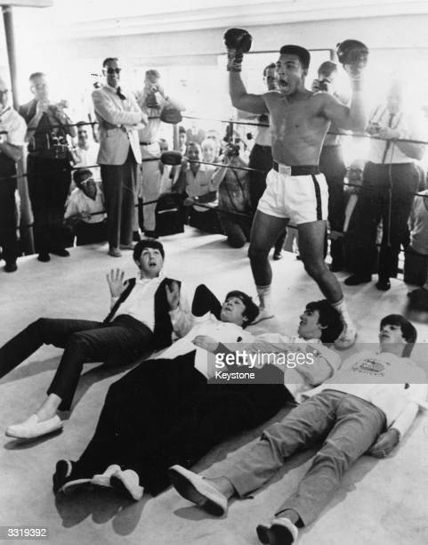 American heavyweight boxer Cassius Clay poses in the ring in mock victory over British pop group The Beatles, meeting the press in New York during an...