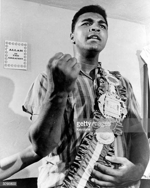 Cassius Clay posing with his belt in front of a sign 'Allah is the Greatest' in his apartment in Miami before his title fight with Sonny Liston for...