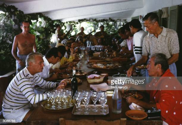 A long afternoon lunch at Acapulco Among the guest are film star Douglas Fairbanks Junior couturiers Oscar de la Renta and standing behind him Emilio...