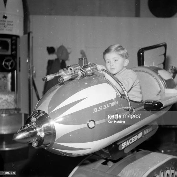 A child indulges his fantasies in the SS Saturn a spaceship ride at a London exhibition of fairground equipment
