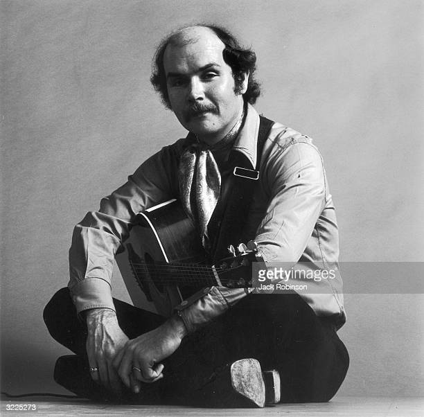 EXLCUSIVE Fulllength studio portrait of American folk singer and songwriter Tom Paxton sitting crosslegged with his acoustic guitar