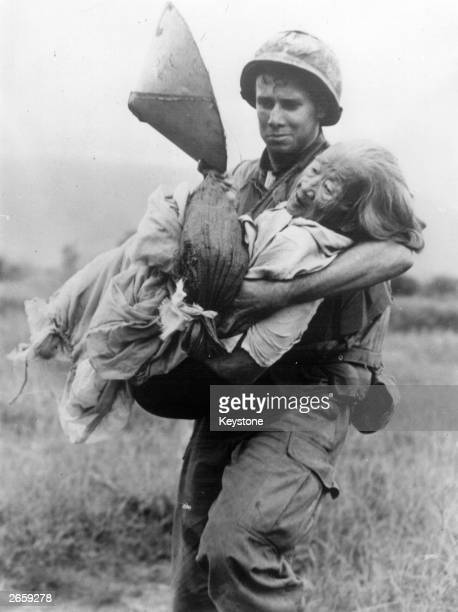 Lance Corporal Charles C Sead of Portsmouth Ohio carries an elderly Vietnamese woman too old to keep up with the patrol in the Arizona Territory 22...