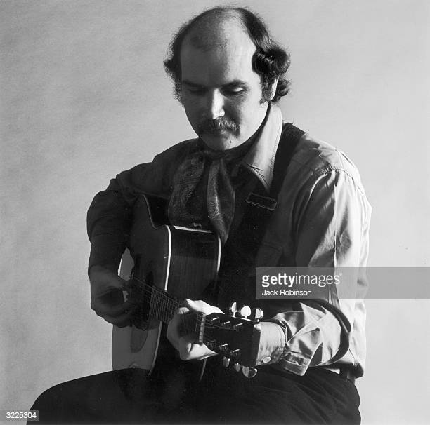 Studio portrait of American folk singer and songwriter Tom Paxton sitting and playing his acoustic guitar