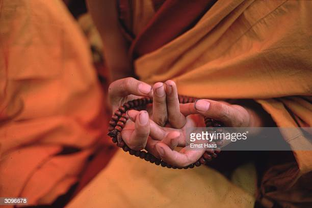 Buddhist monk uses a trenwa to form the symbolic opening of the wisdom, or third eye and the mandala mundra, or symbol of the universe, during the...