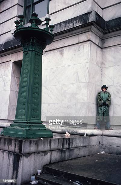 A mardi gras figure in hat mask and long green coat stands in the corner of a white marble building in New Orleans