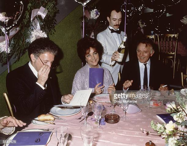British actress Elizabeth Taylor sitting next to her husband Richard Burton at her 50th birthday.
