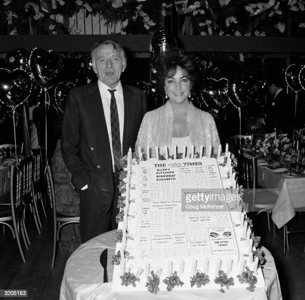 Welsh actor Richard Burton with his exwife Elizabeth Taylor at her 50th birthday party Taylor's birthday cake is decorated to look like the front...