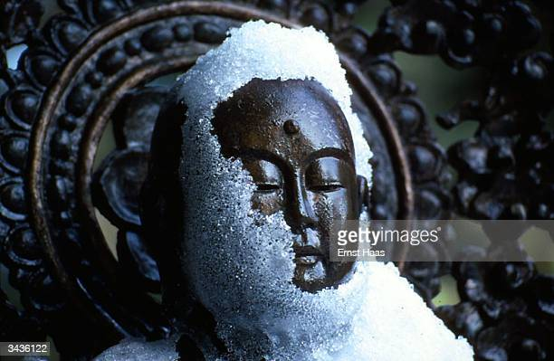 A statue of Buddha in the snow at the Shingon monastery of Koyasan Japan