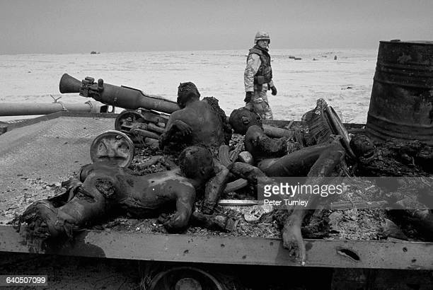 A few days after the end of the Gulf ground war an American soldier inspects the carbonized bodies of Iraqi soldiers on the flat bed of a truck who...