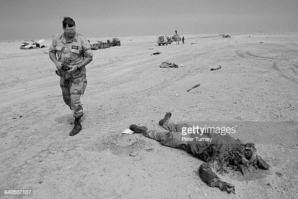 A few days after the end of the Gulf ground war an American soldier looks at a dead Iraqi soldier lying in the desert near where his convoy of...