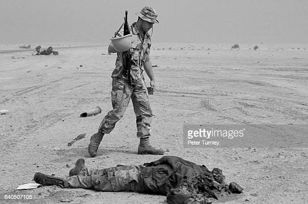 A US soldier looks over the decapitated corpse of an Iraqi soldier