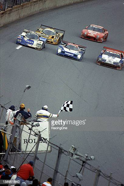 At Daytona International Speedway the winning Nissan R91CP is sandwiched between two other competitors as the checkered flag falls to end the Rolex...